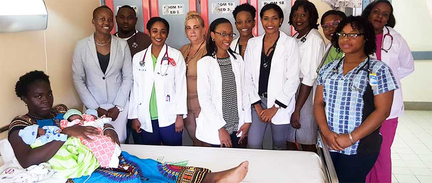 Image of nurses and doctors who performed the triplets miracle around the bed of mother and infants.
