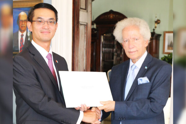 Image of Governor General, His Excellency Sir Emmanuel Neville Cenac, accepting the Letters of Credence from Ambassador Chen.