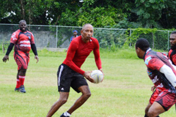 Image: Wayne Pantor with ball in hand showing some of yesteryear brilliance versus Whiptail Warriors; Wayne takes charge of the encounter as Referee. (PHOTO: Anthony De Beauville)