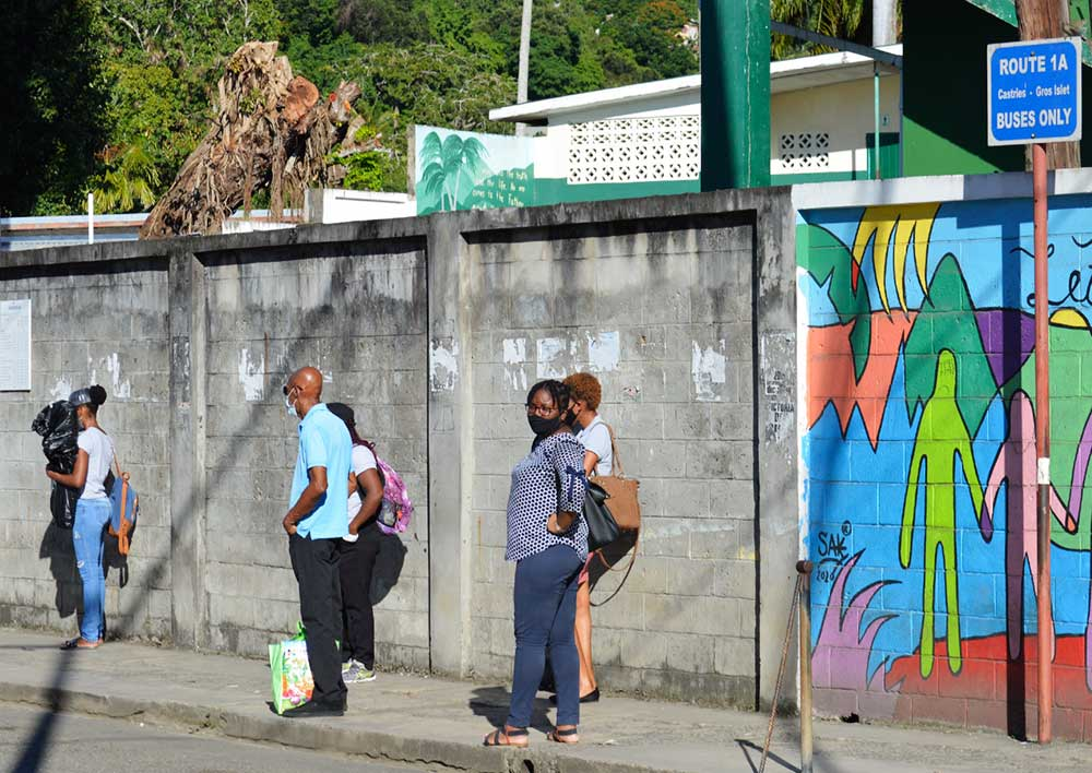 Image: Commuters waiting for a bus at an empty Gros Islet bus terminal Tuesday. (PHOTO: Anthony De Beauville)