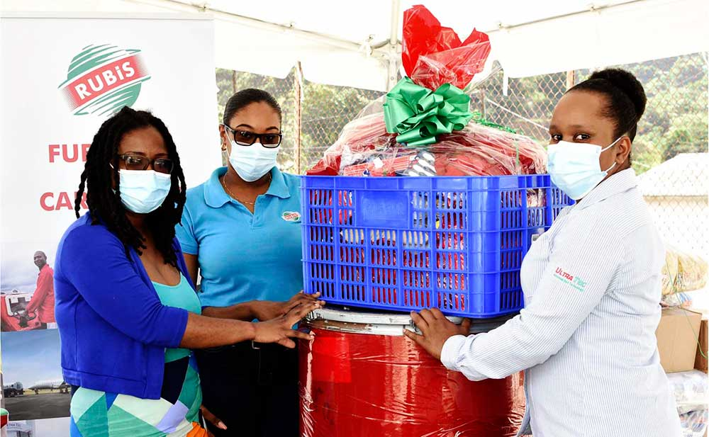 Image: (L-R) Alisha St Martin, Field Officer at the NCPD accepts a Christmas hamper from Chriselda Norbal and Vernesa Joseph of RUBIS.