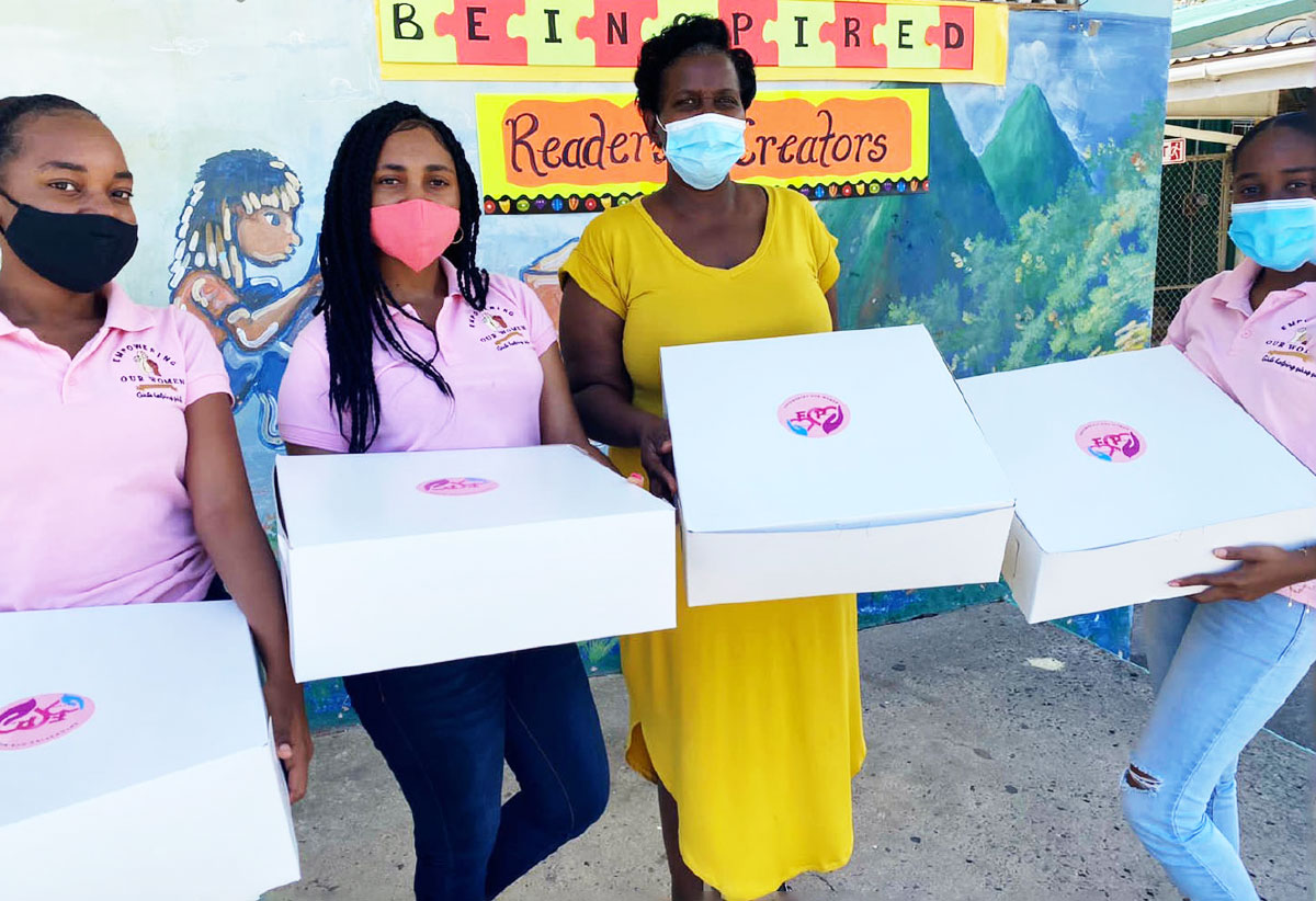 Image: Members of the group with the principal of the prinsipal of the Soufriere Primary School ready to distribute Fem-pacs.