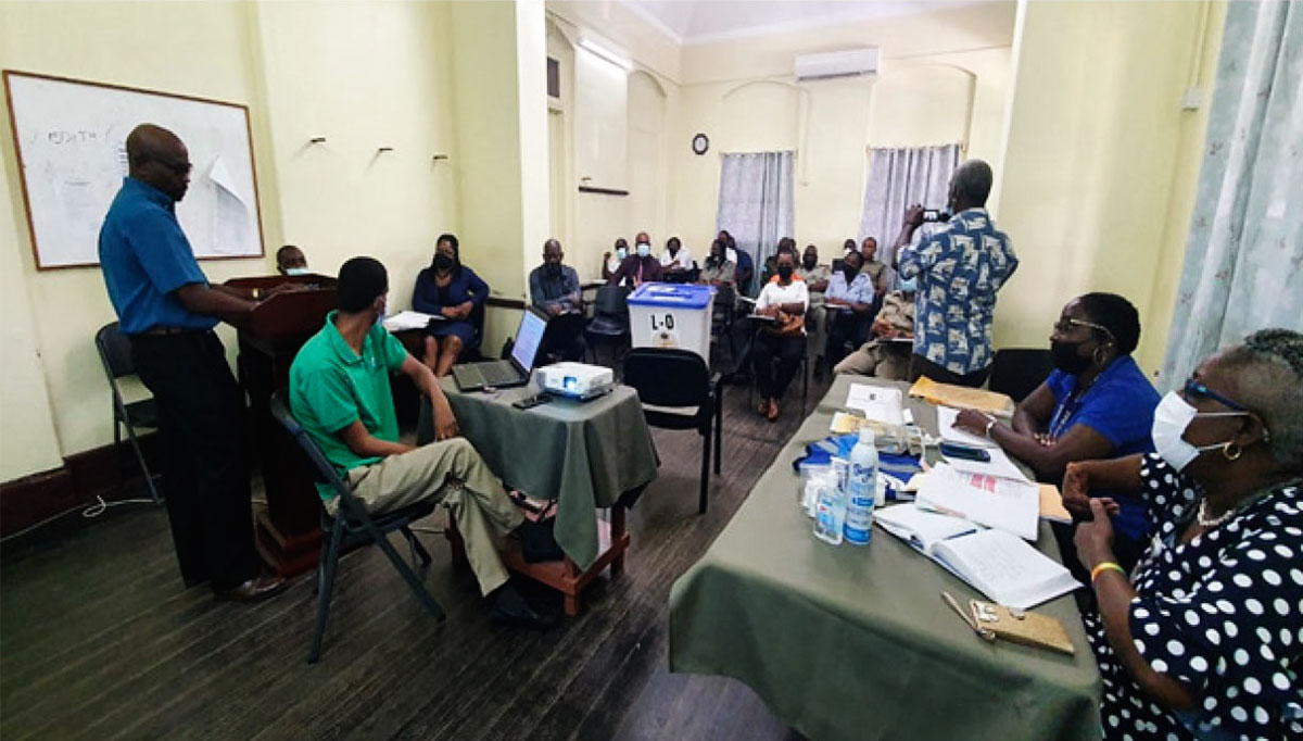Police officers and electoral department officials at a meeting.