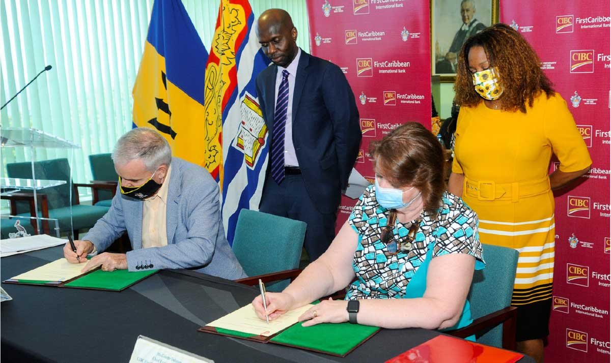 CIBC FirstCaribbean's Chief Executive Officer Colette Delaney signs a copy of the MOU as does Principal of the Cave Hill campus of the UWI, Professor Clive Landis while the bank's Director of Corporate Communications Debra King and Deputy Principal of Cave Hill campus Professor Winston Moore observe.