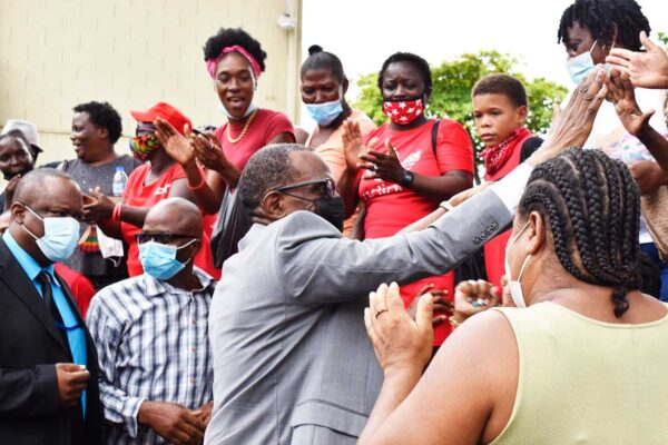 Prime Minister Philip J Pierre high-fiving supporters