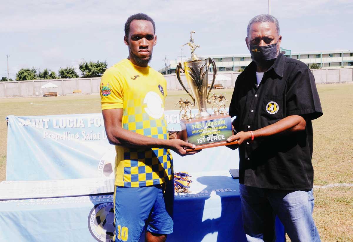 Platinum FC captain Gregson President (L) holding the Chmpionship trophy.