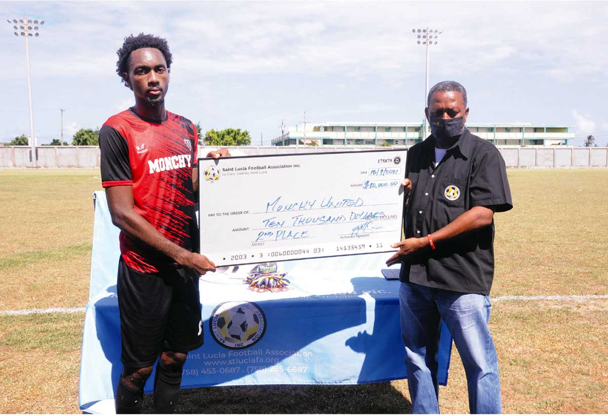 SLFA's Lyndon Cooper presents cheque to runners-up Monchy FC Skipper Otev Lawrence.