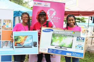 This raffle winner (centre) was all smiles as she received her prizes from Massy Store reps.